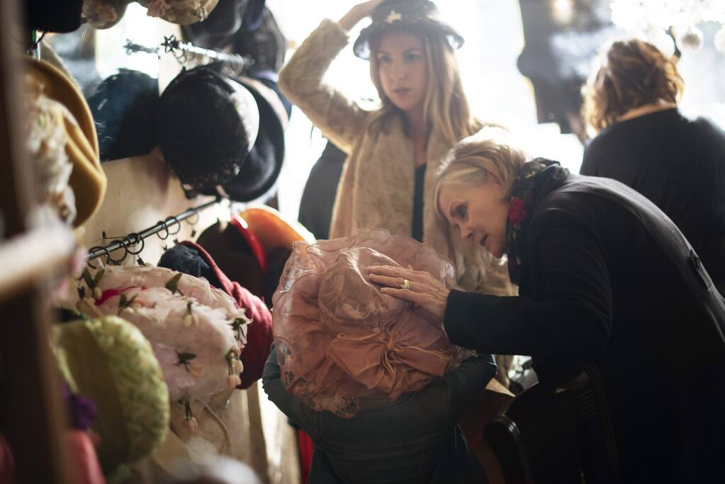 Kathy Negri, right, helping Stella Rose Negri, 5, choose a hat while her mother Liz Negri makes a choice from a large hat collection offered to guests during a Mary Poppins Etiquette Tea Party held Sunday at Tudor Rose English Tea Room in downtown Santa Rosa, California. December 23, 2018.(Photo: Erik Castro/for The Press Democrat)