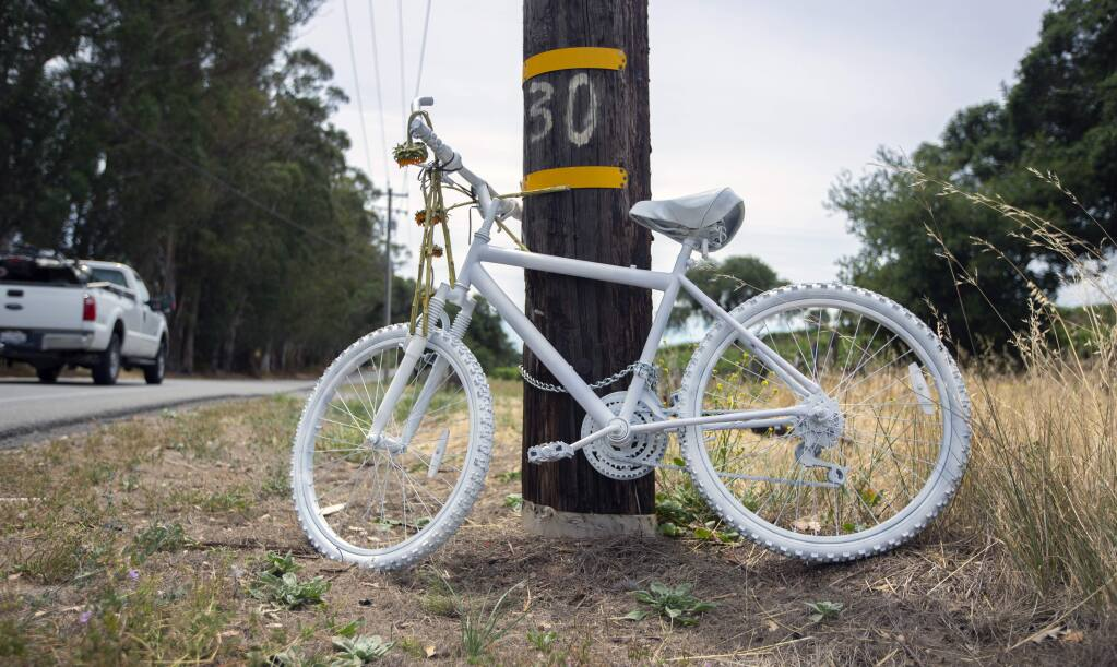 "A bicycle painted gray, chained to a power pole on Highway 12, where a bicyclist was the fatal victim of a hit and run. Among bicyclists, it is known as a ""ghost bike,"" and is placed at the scene of every fatal bicycle accident as a tribute to and remembrance of the rider.(Photo by Robbi Pengelly/Index-Tribune)"