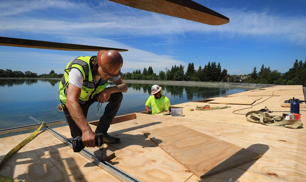 Tyger Roy, left and Shane Cook assemble platforms that will be used to to piece together solar panels on floats that will be floated in to one Windsor's effluent ponds, Wednesday, June 5, 2019. (Kent Porter / The Press Democrat) 2019