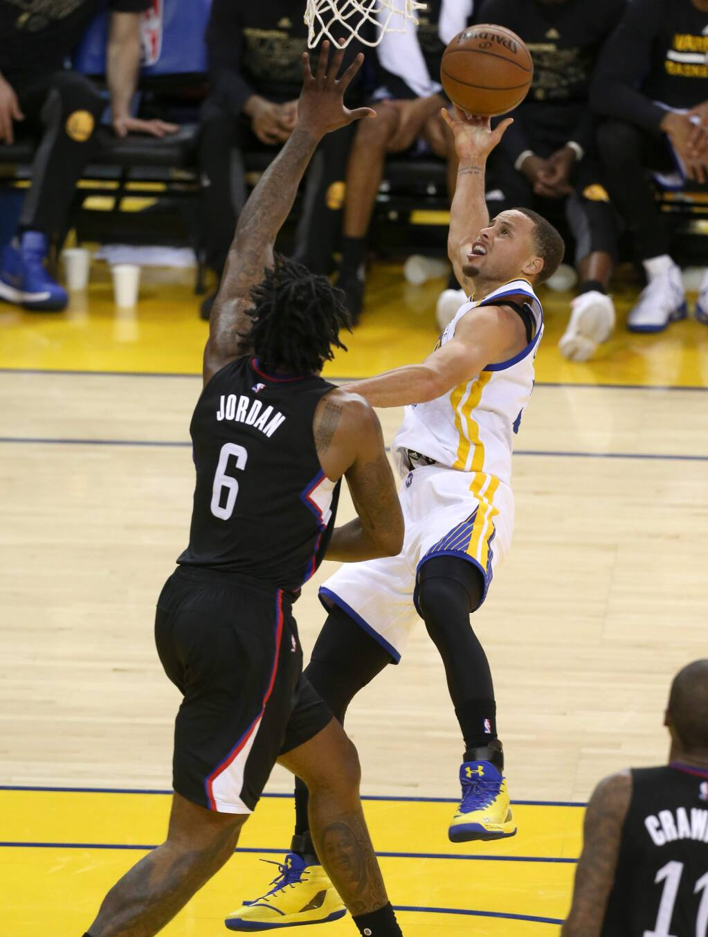 Golden State Warriors' Stephen Curry is fouled by Los Angeles Clippers' DeAndre Jordan as he goes to the basket in Oakland on Thursday, February 23. (Christopher Chung/ The Press Democrat)