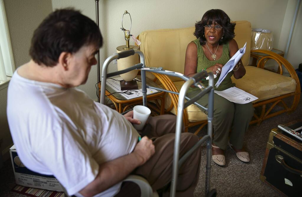 Caregiver Emelia Locke reads and explains Gary Fairburn's mail to him at his apartment in Santa Rosa, on Tuesday, June 9, 2015. (Christopher Chung/ The Press Democrat)