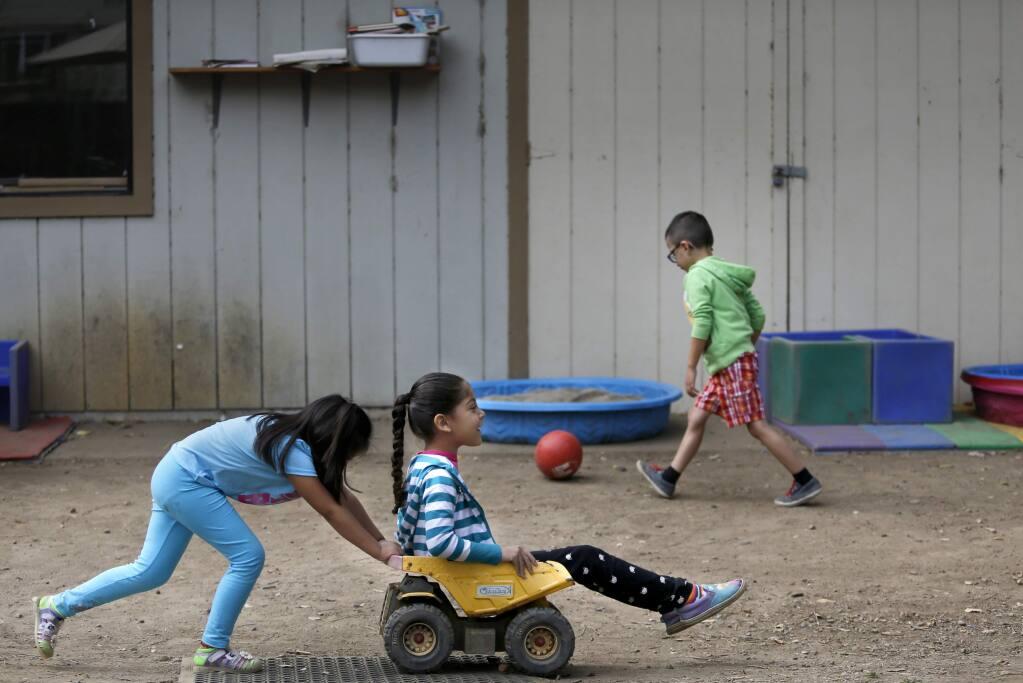Estrella Palencia, 5, pushes Mezmerae Davenport, 5, around the schoolyard at Healdsburg Child Development Preschool in Healdsburg, on Tuesday, August 11, 2015. (BETH SCHLANKER/ The Press Democrat)