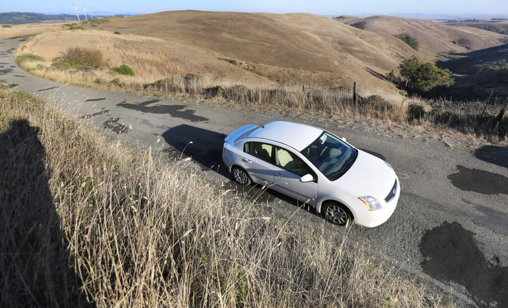 A car makes its way over filled-in potholes on Bay Hill Road east of Bodega Bay. (KENT PORTER/ PD FILE, 2013)