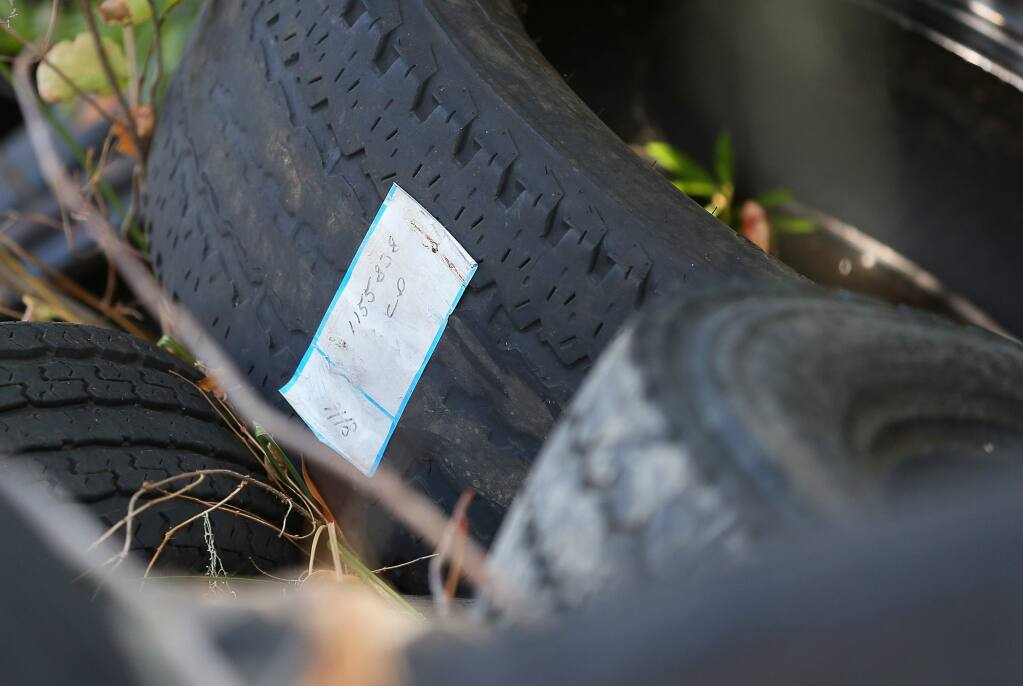 A tire with a label attached is among a large number of tires dumped along Highway 101 and the Russian River, four miles south of Hopland, on Tuesday, October 1, 2019. (Christopher Chung/ The Press Democrat)