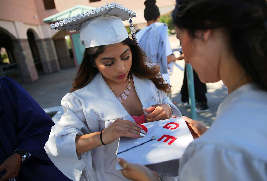 Katherine Beltran, left, helps Geovani Flores decorate her mortar board before the Elsie Allen commencement ceremony, in Santa Rosa on Friday, June 3, 2016. (Christopher Chung/ The Press Democrat)