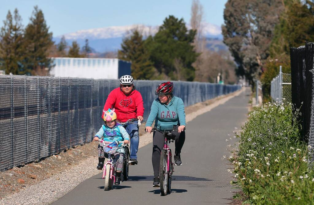 Evelia, right, Luis Castaneda, and their daughter Lily, 5, ride their bikes along the existing shared use path along the SMART tracks, north of Bellevue Avenue, in Santa Rosa on Monday, February 18, 2019. An extension of the shared use path south of Bellevue Avenue is part of a new master plan for bike routes and walking paths before the planning commision.(Christopher Chung/ The Press Democrat)