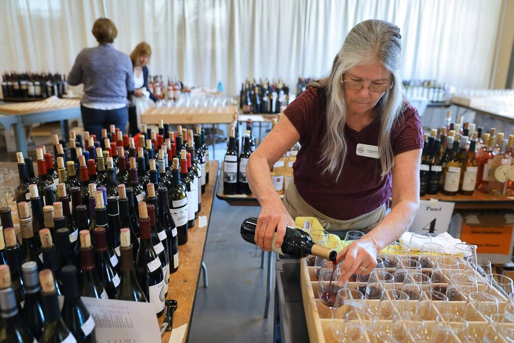 Annabel Bentley prepares glasses of wine for judging during the North Coast Wine Challenge in Santa Rosa on Tuesday, April 9, 2019. (Christopher Chung/ The Press Democrat)