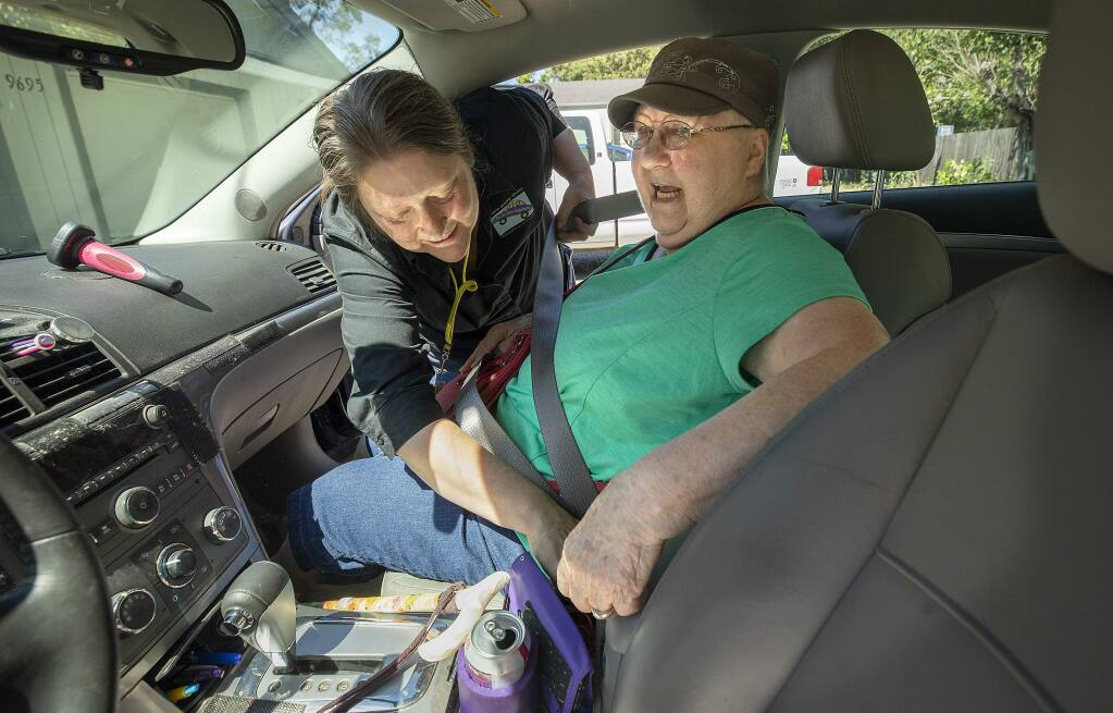 Renee Cooper, owner of Women Driving Women, fastened the seatbelt for customer Pat Hellhacke, 77, before driving her from her Windsor home to a chemotherapy appointment at Kaiser Hospital in Santa Rosa on Wednesday. (photo by John Burgess/The Press Democrat)