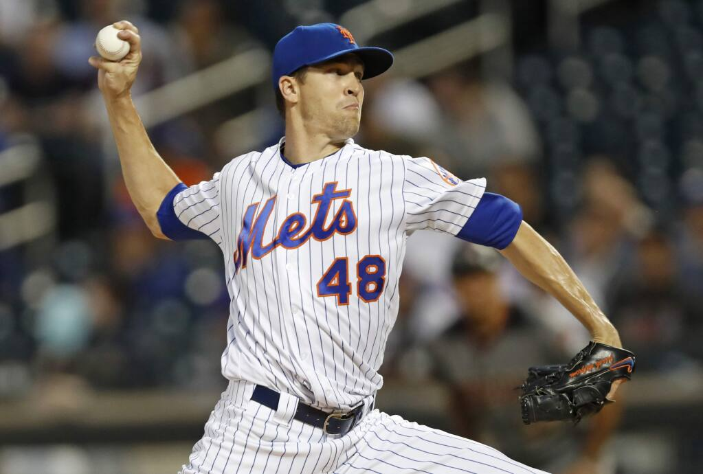 In this Sept. 9, 2019, file photo, New York Mets starting pitcher Jacob deGrom winds up during the first inning against the Arizona Diamondbacks in New York. DeGrom has been named the NL Cy Young Award winner for the second straight year. (AP Photo/Kathy Willens, File)