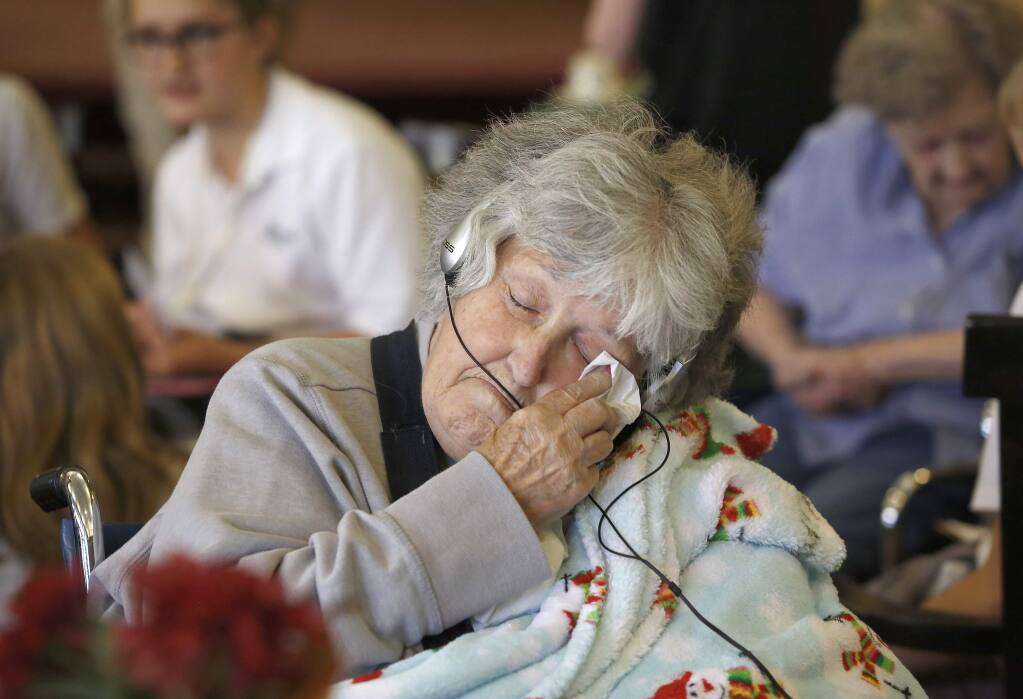 Dolores Kovocovich wipes away a tear while listening to music provided by The Healdsburg School students at Healdsburg Senior Living. (Beth Schlanker / The Press Democrat)