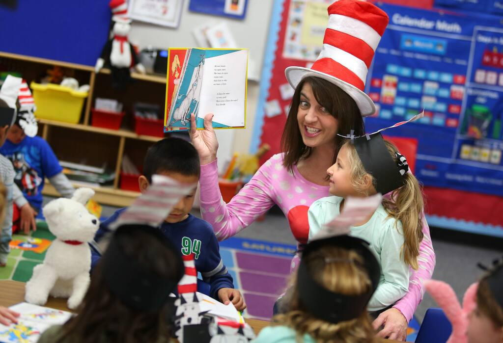 Transitional kindergarten teacher Michele Ferretti, center, reads Dr. Seuss' 'One Fish Two Fish Red Fish Blue Fish' to Ava Roach, right, David Vasquez-Valentin, and other students in her class, during Read Across America at Mattie Washburn elementary school, in Windsor on Monday, March 2, 2015. (Christopher Chung/ The Press Democrat)