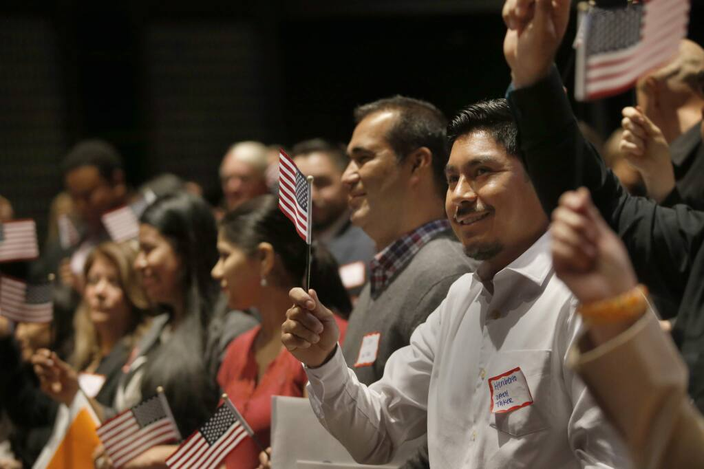 Mexican immigrant Heriberto Herrera reacts after taking the Oath of Allegiance during a U.S. naturalization ceremony at the Napa Valley College Performing Arts Center on Thursday, March 31, 2016 in Napa, California . (BETH SCHLANKER/ The Press Democrat)