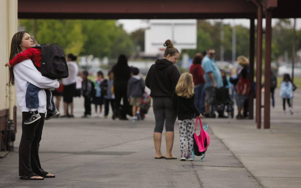 Shauna Wagner held Shyler Medeiros, 7, until the bell rang. He had a tough time coming back to school for his first day in first grade at McDowell Elementary. (CRISSY PASCUAL/ARGUS-COURIER STAFF)