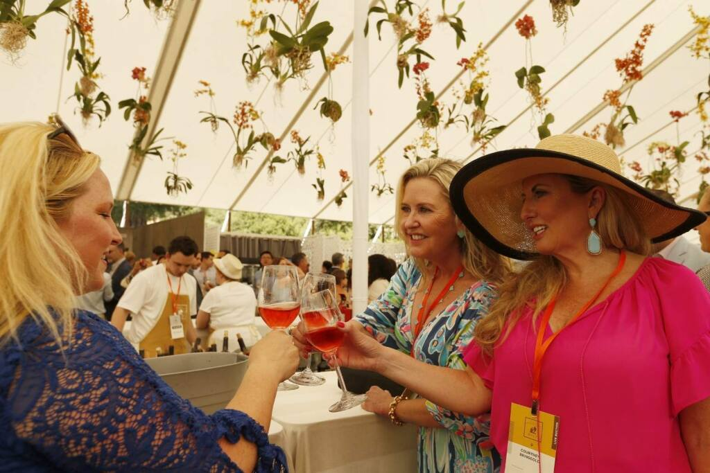 Lisa Covey of Yountville, left, toasts sisters Kimberly and Courtney Bringgold, both of Newport Beach, during Auction Napa Valley at Meadowood Resort in St. Helena, Calif., on Saturday, June 3, 2017. (Alvin Jornada / The Press Democrat)