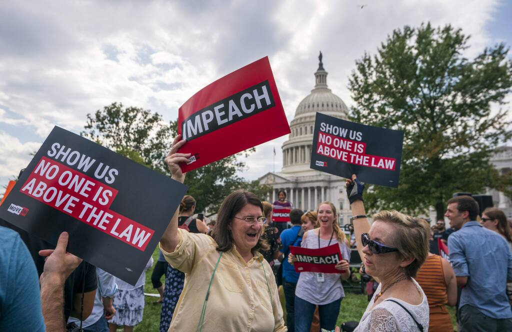 Activists rally for the impeachment of President Donald Trump, at the Capitol in Washington, Thursday, Sept. 26, 2019. Speaker of the House Nancy Pelosi, D-Calif., committed Tuesday to launching a formal impeachment inquiry against Trump. (AP Photo/J. Scott Applewhite)