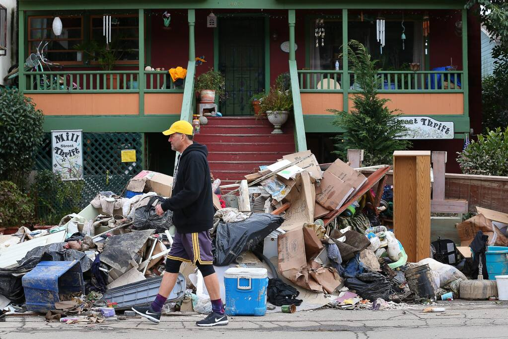 Jack Seely walks past a pile of flood damaged materials along Mill Street in Guerneville on Monday, March 4, 2019. (CHRISTOPHER CHUNG/ PD)