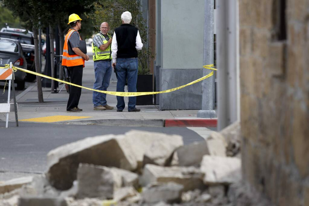 (From left) Structural engineer Lawrence Jones and general contractor Ed James help Doyle Wiseman evaluate the condition of his building Main Street West across from the severely damaged Pfeiffer Building building following Sunday's earthquake on Monday, August 25, 2014 in Napa, California. (BETH SCHLANKER/ The Press Democrat)