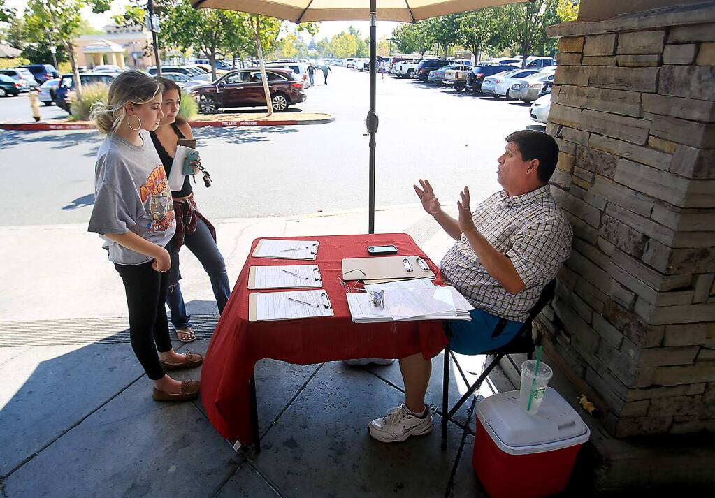 Declining to give his name, a petitioner talks to prospective signers about attempting to get Santa Rosa's rent control overturned, Wednesday Sept. 8, 2016 in front of Safeway on Mendocino Ave. in Santa Rosa. (Kent Porter / The Press Democrat) 2016