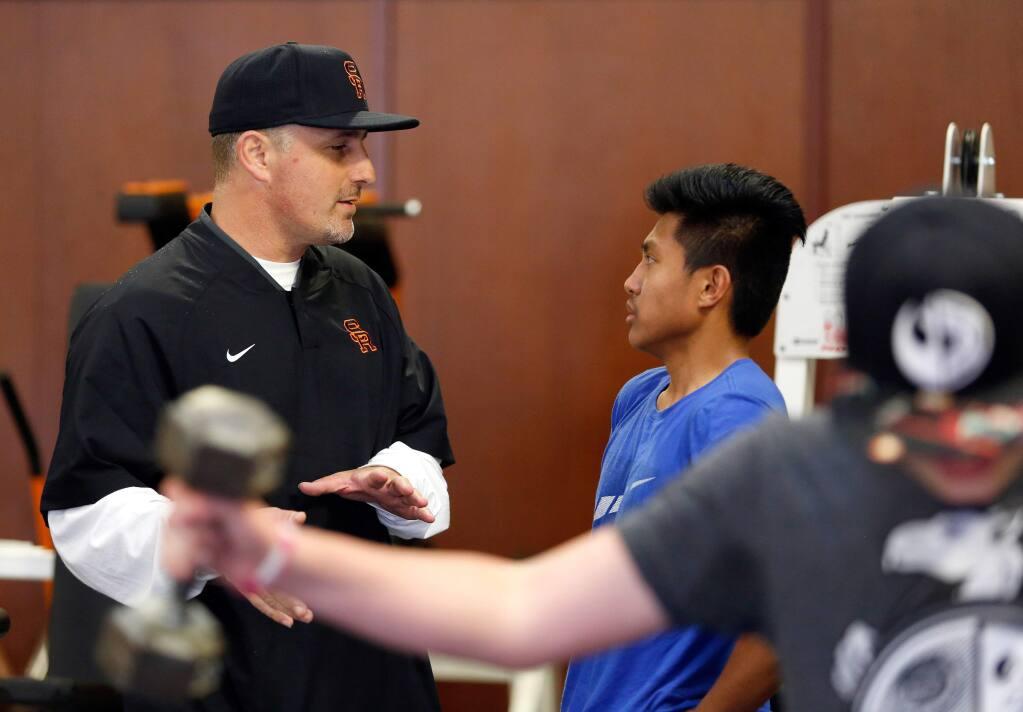 Santa Rosa High School varsity football coach Russell Ponce, left, talks with junior receiver/cornerback Joseph Liberato in the Santa Rosa High School weight room in Santa Rosa on Tuesday, April 11, 2017. (ALVIN JORNADA/ PD)