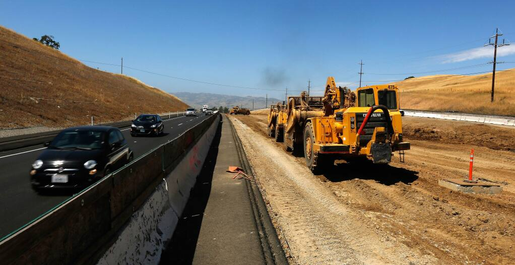 Motorists drive southbound on Highway 101 as wheel tractor-scrapers, right, grade the soil in the highway median, south of Petaluma, California in 2018. (Alvin Jornada/The Press Democrat)