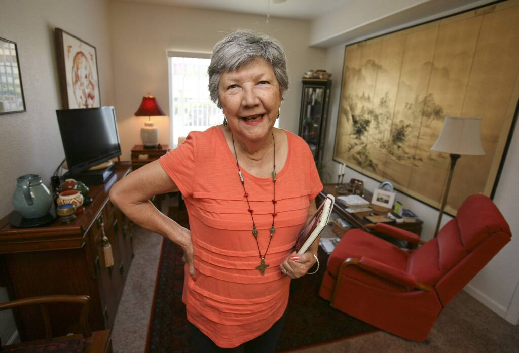 Author Helen Mossman, holds the book she wrote about the two years she spent hiding in the jungle from Japanese soldiers during WWII, in her Petaluma home on Monday September 15, 2014. (SCOTT MANCHESTER/ARGUS-COURIER STAFF)