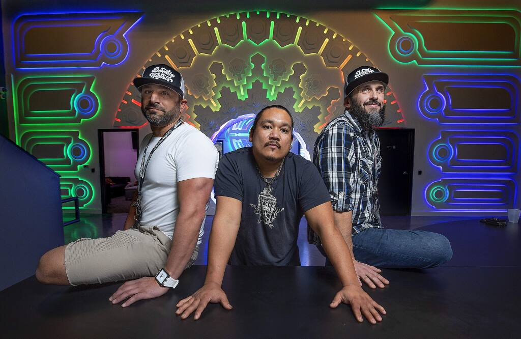 Co-owners Brandon Levine, left, and Damon Crain, right, with creative and technical director Donnie Penales in the check-in room at the new Doobie Nights marijuana dispensary in Santa Rosa. (photo by John Burgess/The Press Democrat)
