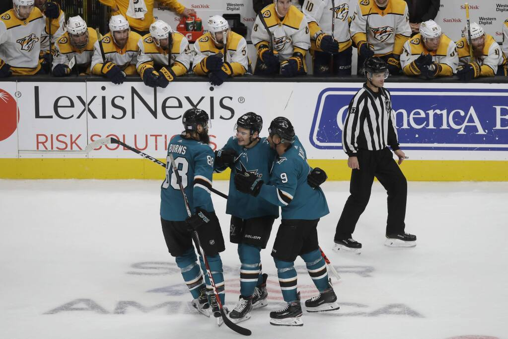 Nashville Predators players, top, watch as San Jose Sharks right wing Timo Meier, bottom center, is congratulated by defenseman Brent Burns, left, and left wing Evander Kane after scoring in the shootout in San Jose, Saturday, Nov. 9, 2019. The Sharks won 2-1. (AP Photo/Jeff Chiu)