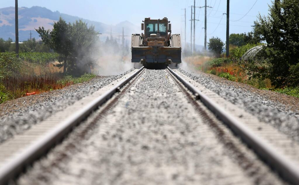 A machine distributes ballast on the Sonoma-Marin Area Rail Transit line between Fulton and San Miguel roads in Santa Rosa in July 2014. (Christopher Chung / The Press Democrat)