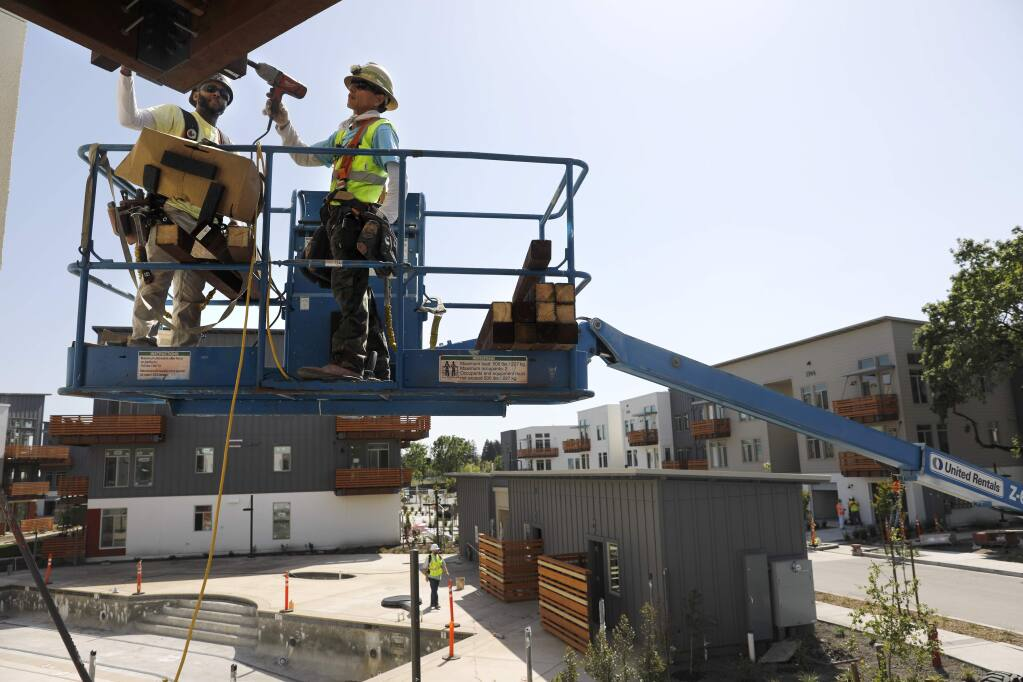 Ramon Avellar, left, and Hilario Garcia of Katerra Construction work on building a balcony as they complete new units of the Annadel apartment complex on Monday, April 30, 2018 in Santa Rosa, California . (BETH SCHLANKER/The Press Democrat)