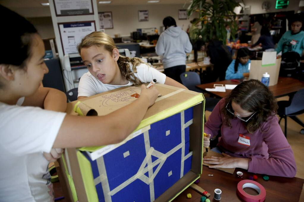 Gia Bettinelli, 11, center, Silvia Olvera, 13, left, and Hannah Berkheimer, 13, work to build a hockey arcade game during the Girls Tinker Academy in the makerspace on the Sonoma State University campus in Rohnert Park on Monday, July 30, 2018. (Beth Schlanker/ The Press Democrat)