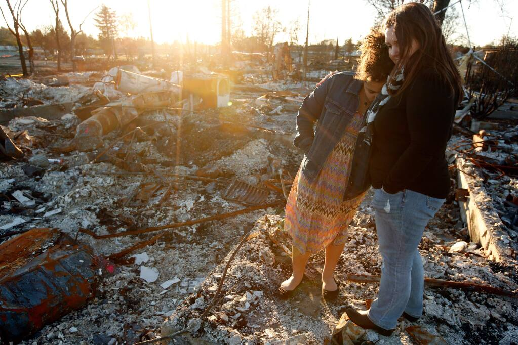 Amy Marlar embraces her daughter Logyn, 11, as they stand on what used to be the front porch of their Santiago Drive home that was destroyed by the Tubbs Fire, in the Coffey Park neighborhood of Santa Rosa, California on Wednesday, December 20, 2017. (Alvin Jornada / The Press Democrat)