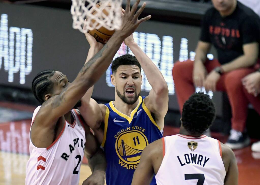 Golden State Warriors guard Klay Thompson (11) looks for the pass under pressure from Toronto Raptors guard Kyle Lowry (7) and teammate Kawhi Leonard (2)during the first half of Game 2 of basketball's NBA Finals, Sunday, June 2, 2019, in Toronto. (Frank Gunn/The Canadian Press via AP)