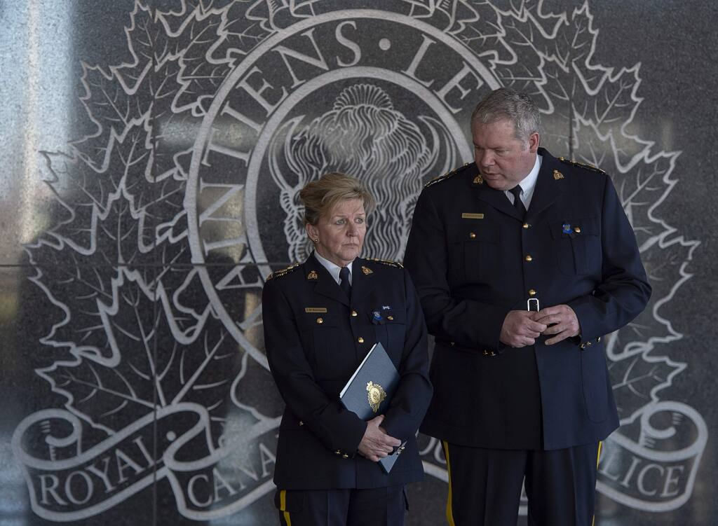Royal Canadian Mounted PoliceP Assistant Commissioner Lee Bergerman, left, and Chief Superintendent Chris Leather wait for the start of a news conference at RCMP headquarters in Dartmouth, Nova Scotia on Sunday, April 19, 2020. (Andrew Vaughan/The Canadian Press via AP)