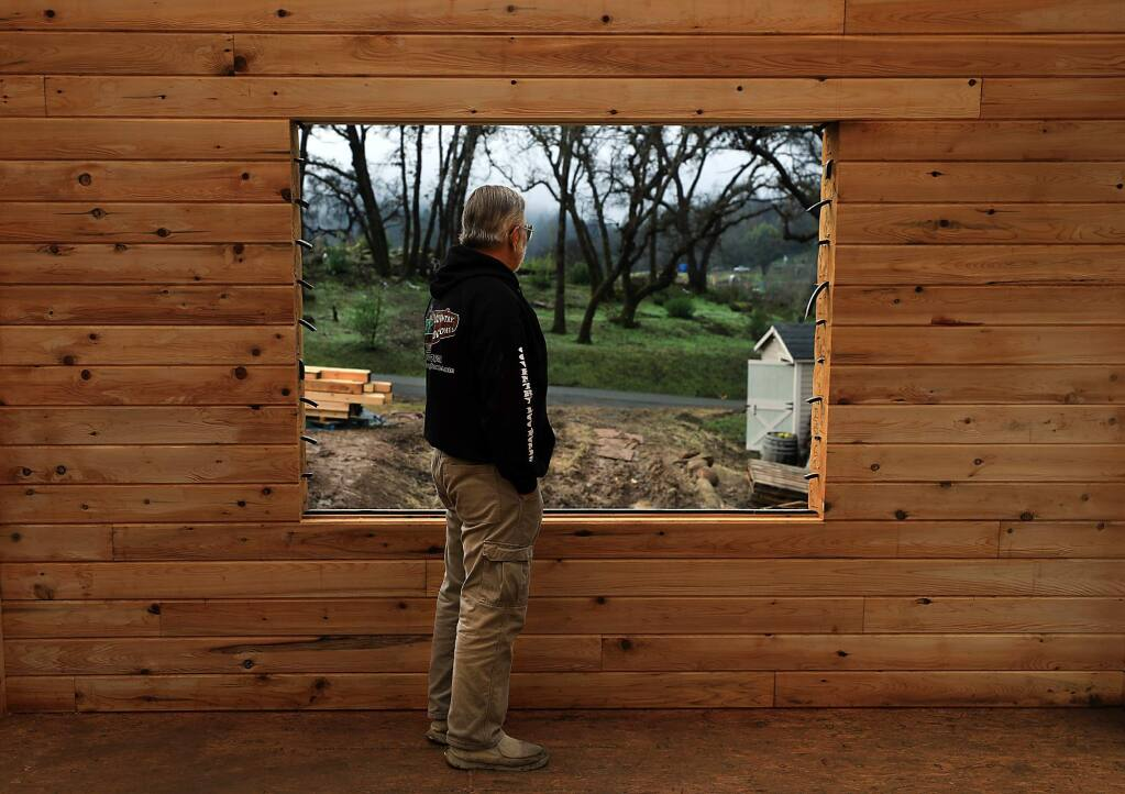 Gary Bayless contemplates the rebuilding of his log home in the Mark West area, Wednesday, Dec. 19, 2018. The Bayless home was razed during the Tubbs fire. (Kent Porter / The Press Democrat) 2018