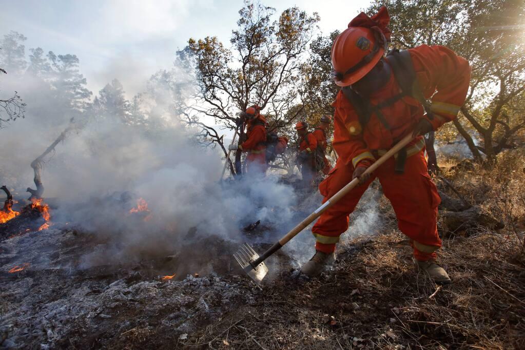 Inmate Don'jai Hilbert of Cal Fire Mt. Bullion Inmate Crew 2 helps extinguish a hot spot at the Oakmont fire in Santa Rosa, California on Tuesday, October 17, 2017. (Alvin Jornada / The Press Democrat)