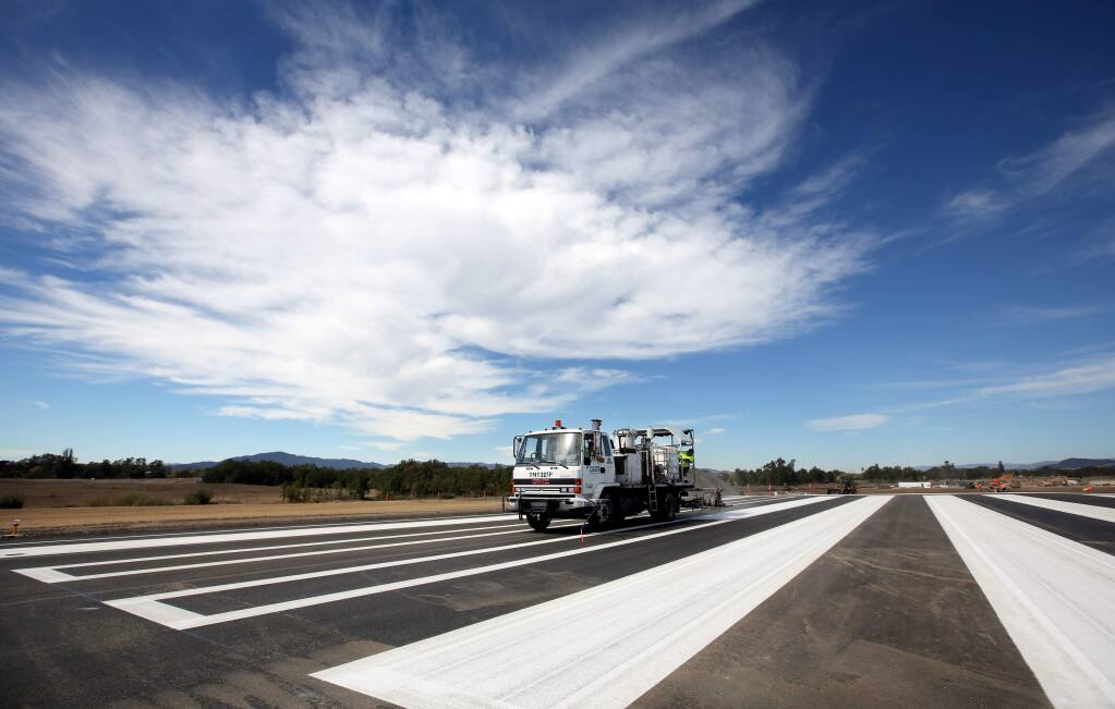 Maxwell Ashpalt paints the stripes during construction of the runway expansion project at the Charles M. Schulz-Sonoma County Airport on Tuesday, Oct. 7, 2014. (CRISTA JEREMIASON/ PD)