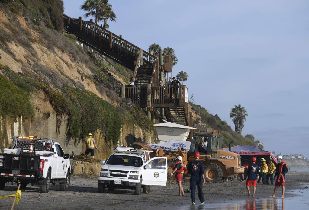 FILE - In this Friday, Aug. 2, 2019 lifeguards and search and rescue personnel work at the site of a cliff collapse at a popular beach in Encinitas, Calif. Three family members enjoying a day at a San Diego area beach were killed Friday when a huge slab of the cliff above plunged on to the sand. The collapse has raised questions about the stability of bluffs along California's 1,000-mile (1,600-kilometer) coast. (AP Photo/Denis Poroy, File)