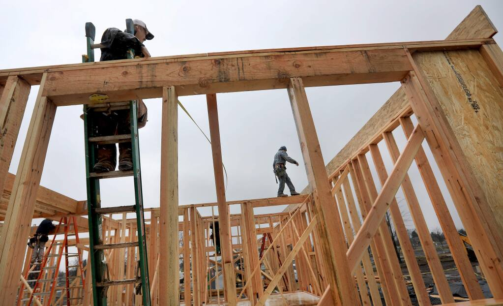 Workers with Pierre Homes prepare to put the second floor on an Astaire Court home in Coffey Park, Friday March 2, 2018 in Santa Rosa. (Kent Porter / Press Democrat) 2018