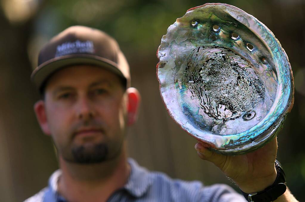 Abalone Diver Owen Mitchell of Cotati displays an abalone from a past expedition to the Sonoma Coast, Friday March 31, 2017. (Kent Porter / The Press Democrat) 2017
