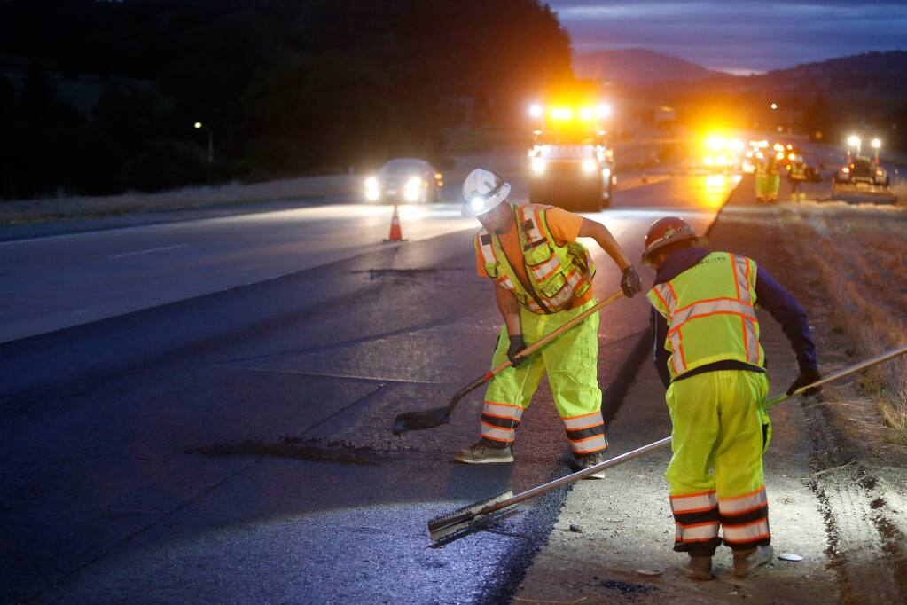 Christopher Mann, left, and Luis Perez of DeSilva Gates Construction follow behind a paving machine and fill holes in the base layers of asphalt their crew is applying on the number one lane of southbound Highway 101 near Geyserville, California, on Wednesday, May 16, 2018. (Alvin Jornada / The Press Democrat)