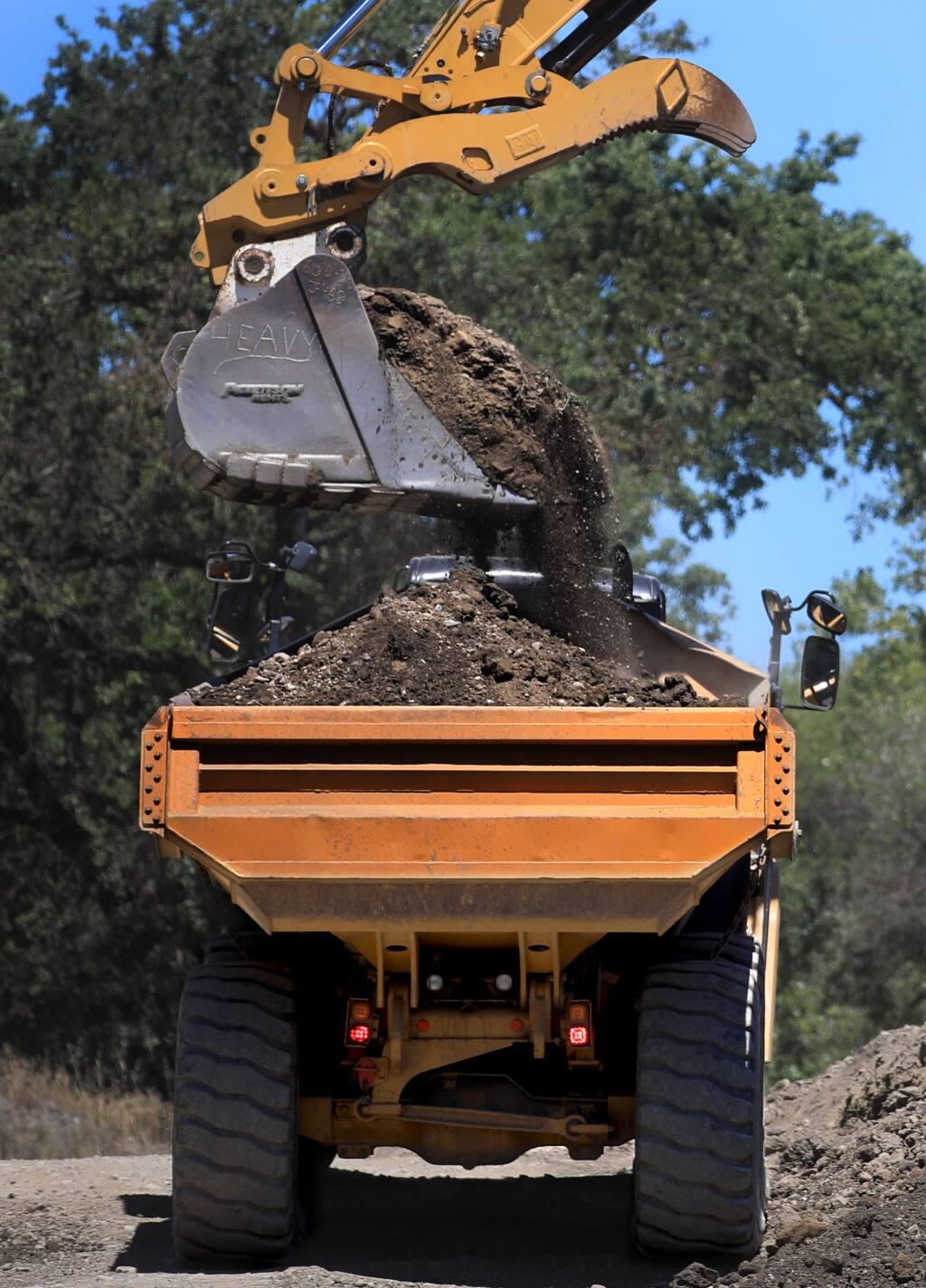 Fill dirt is loaded to be used for the road bed on the Asti summer crossing over the Russian River, Thursday, May 28, 2020 south of Cloverdale, The county is couldn't install a bridge this year, because the river changed course. Officials are looking for a permanent fix. (Kent Porter / The Press Democrat) 2020