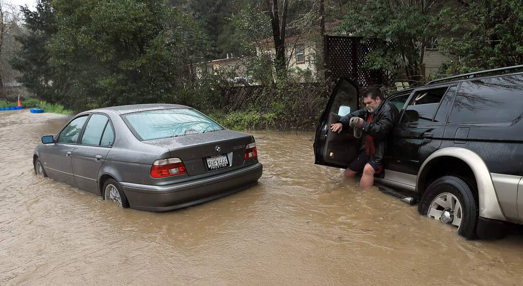 Tim Russell of Guerneville attemped to pull a motorist from Armstrong Woods Road after it became inundated in Guerneville, Tuesday, Feb. 26, 2019, but Russell became stuck himself.(Kent Porter / The Press Democrat) 2019