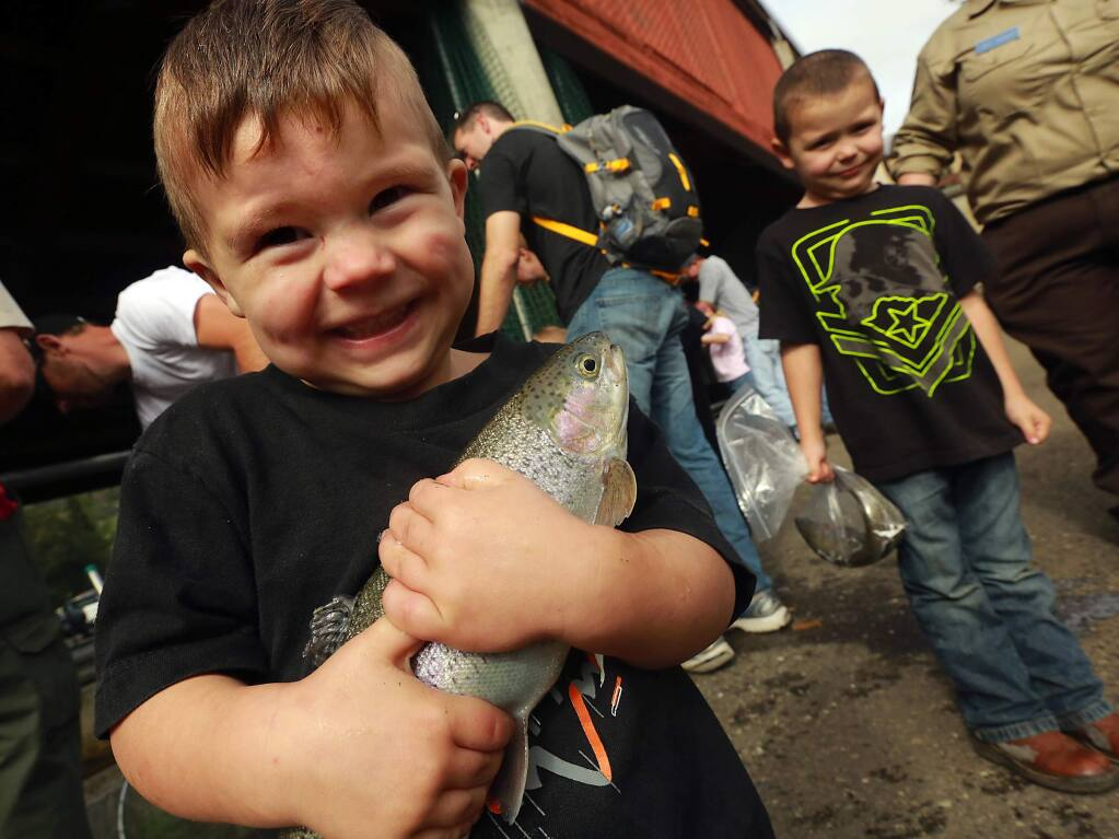 Deegan Mack, 3, of Cloverdale proudly clings to the steelhead fish he caught with his dad and brother Gunner, 5, right, at the Lake Sonoma Steelhead Festival. (Photo by John Burgess/The Press Democrat)