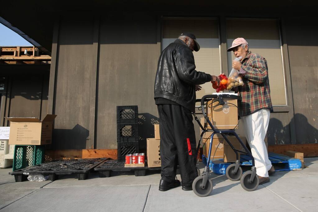 Redwood Empire Food Bank volunteer Pedro Miras helps Alonzo Smith, a homeless senior, fills up a box with food at the Rohnert Park Senior Center in Rohnert Park on Wednesday, Nov. 14, 2018. (BETH SCHLANKER/ The Press Democrat)