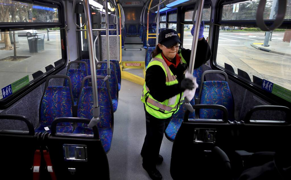 Irma Paredes disinfects the high traffic touch points on Santa Rosa city bus to help limit the possible spread of the novel coronavirus, Friday, March 6, 2020 at the transit mall in Santa Rosa. (Kent Porter / The Press Democrat) 2020