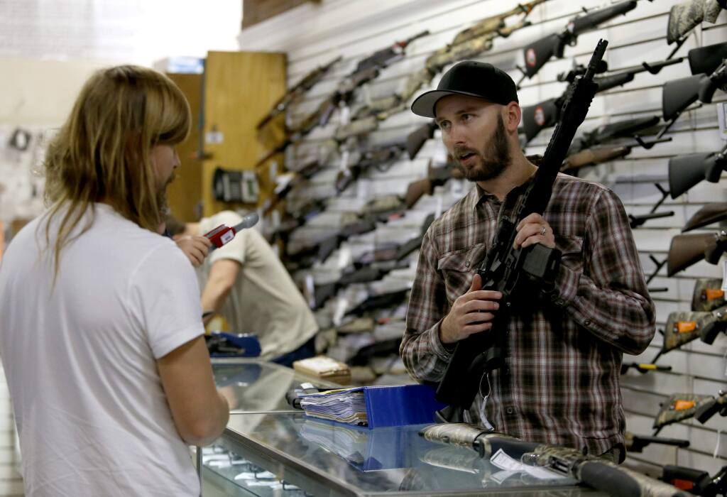 Manager Chris Ostrom talks about the new compliance laws for AR-10 and AR-15 guns with a customer who wished not to give his name at Pacific Outfitters in Ukiah, on Wednesday, December 21, 2016. (BETH SCHLANKER/ The Press Democrat)