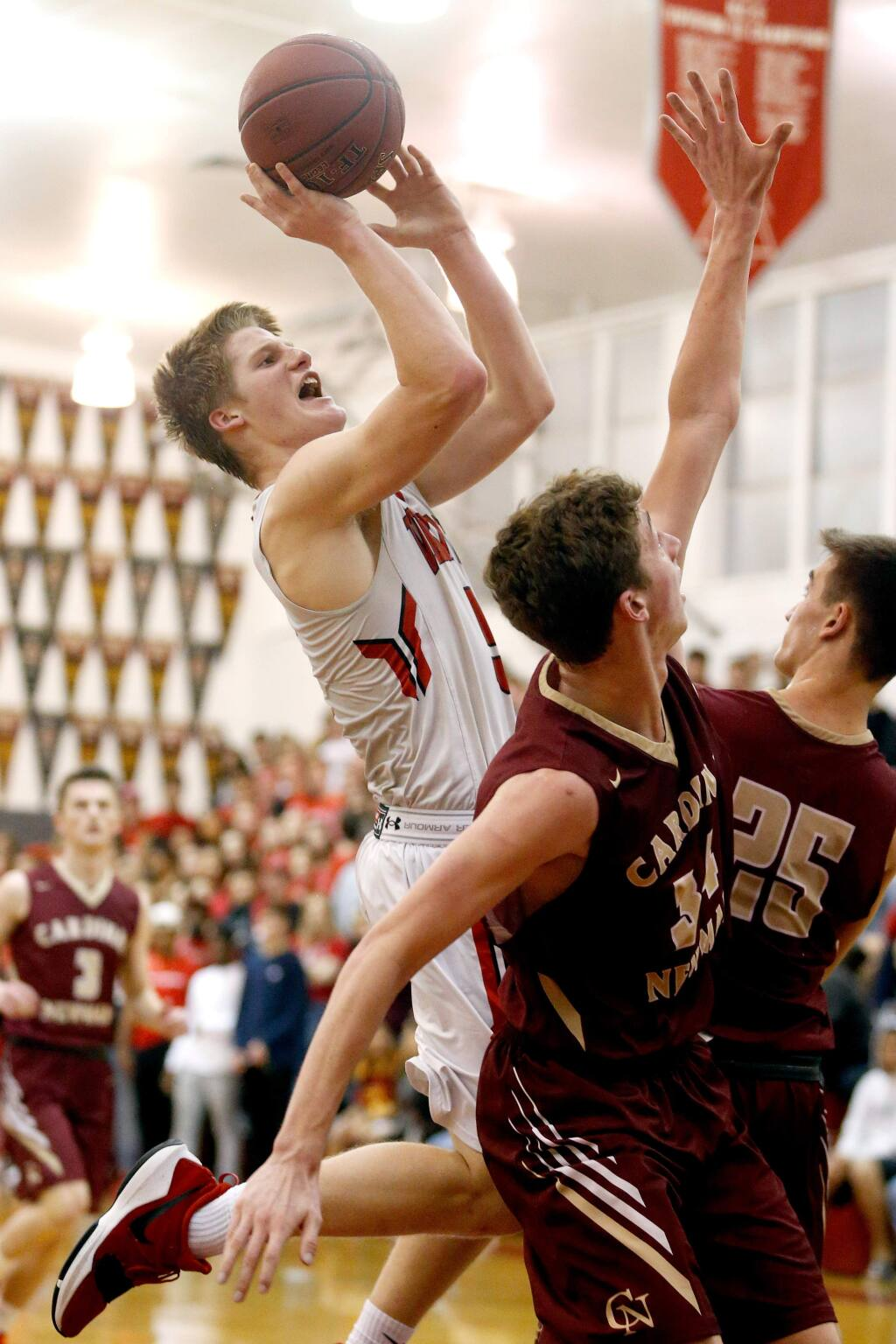 Montgomery's Evan Poulsen (5), left, goes for a shot and draws a foul during the first half of a boys varsity basketball game between Cardinal Newman and Montgomery high school in Santa Rosa, California on Tuesday, January 9, 2018. (Alvin Jornada / The Press Democrat)