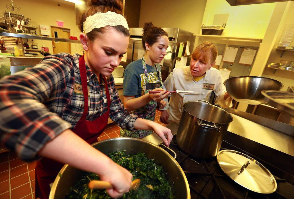 (l to r) Teen chefs Maddie Craig and Christina Alberigi. Donaldson work with mentor Rachel Bloom preparing meals for the seriously ill in the new Ceres Community Project kitchen at SAY's Dream Center. (JOHN BURGESS / The Press Democrat)