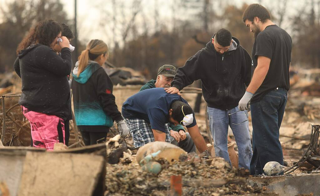 Ben Hernandez, middle, finds their family pet in the ashes of their Hopper Lane home, comforted by his son, Ben jr. with Herenadez's wife Renee, in pink, and the rest of his family, Carlos, Abby, father Ben Sr., in hat, Friday Oct. 20, 2017 in Coffey Park. (Kent Porter / Press Democrat) 2017