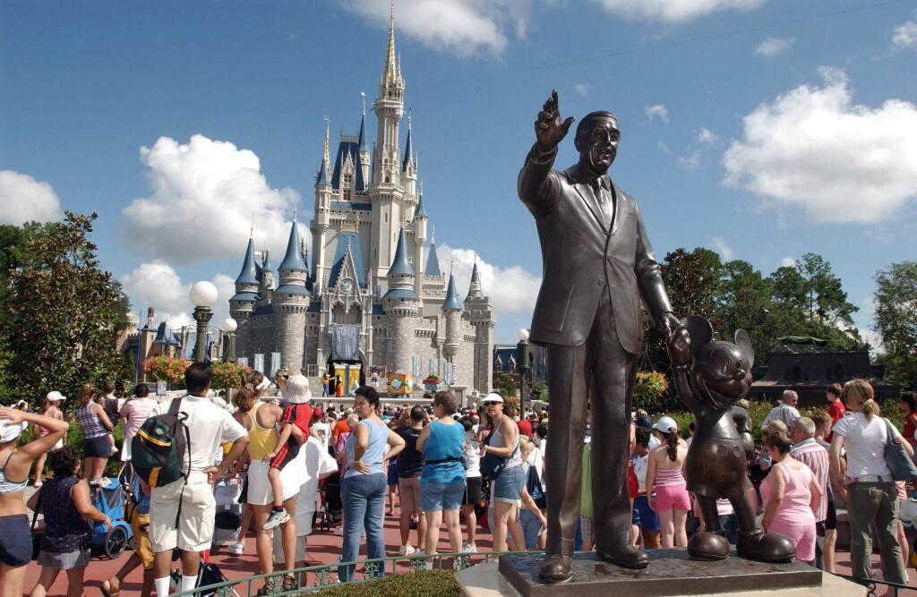 FILE - In this Sept. 2, 2004, file photo, tourists crowd around Cinderella's Castle to watch a performance at Walt Disney World's Magic Kingdom in Lake Buena Vista, Fla. (AP Photo/Phelan M. Ebenhack, File)